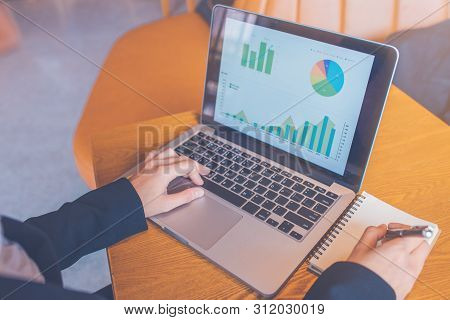 Business Woman Using A Laptop Computer On A Wooden Desk, And She Is Taking Notes On Paper With A Bla