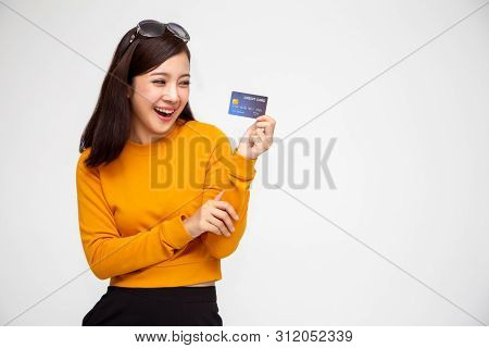 Happy Asian Woman In Yellow Shirt Holding Credit Card Or Cash Advances, Pay Instead Of Money And Spe