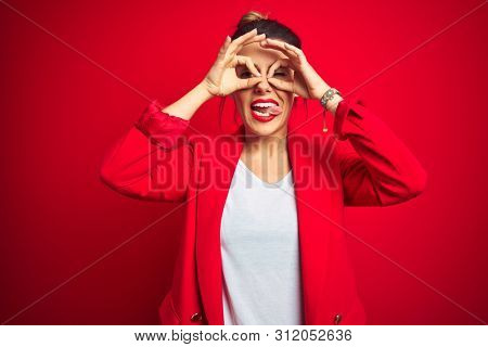 Young beautiful business woman standing over red isolated background doing ok gesture like binoculars sticking tongue out, eyes looking through fingers. Crazy expression.