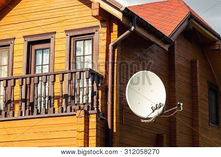 White Parabolic Satellite Antena Dish Hanged On Wall Of Modern Wooden Country House Villa. Wireless