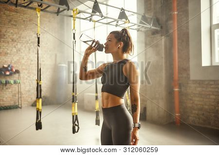 Refreshing. Side View Of Young Athletic Woman In Earphones With Tattoos On Her Hands Is Drinking Wat