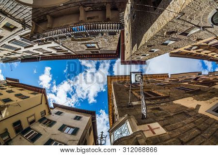 Florence, Italy - May 12, 2019: View Up Among Buildings At A Narrow Intersection In Florence
