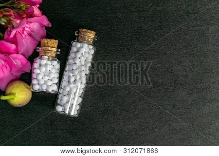Top View Of Two Vintage Homeopathic Medicine Bottles Consisting White Pills With Wild Fruit And Pink