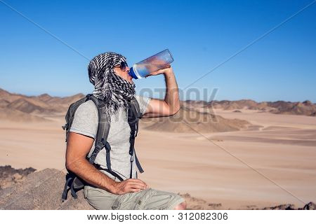Man feels thirst and drinks water in the desert. poster