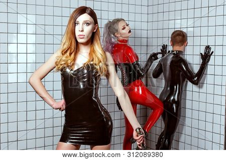 Woman And A Man In Latex Clothes Play An Adult Bdsm Game. A Woman Mocks A Man, She Humiliates A Man.