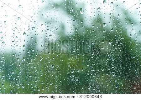 Rain Drops On Rainy Day On Outside Window Glass With Blurred Edges. Rain Outside Window Pane In Spri