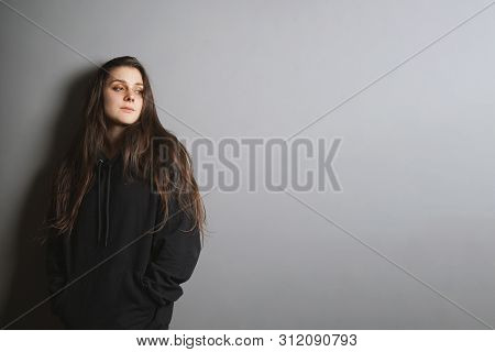 Sad Young Goth Woman Wearing Black Sweater Leaning Against Wall With Her Hands In Pockets And Lookin