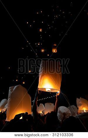 Unrecognizable Man Releasing Paper Lantern During Loi Krathong And Yi Peng Festival In Chian Mai