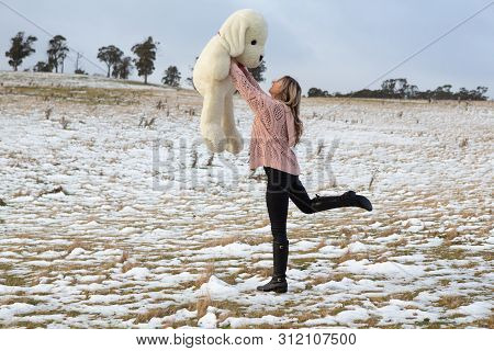 Woman Frolicking In Snow With Stuffed Bear