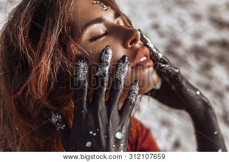 Close Up Of Beautiful Young Woman With Hands Painted Black. Moon And Stars Concept