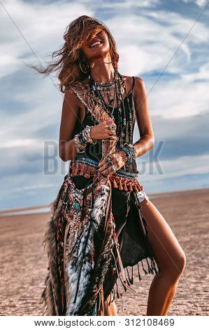 Young Boho Style Woman Sitting On Sand On The Beach At Sunset