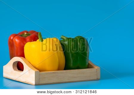 Summer Of Sweet Bell Pepper In Wood Box On Blue Background.