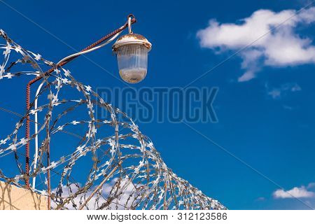 Barbed Wire On A Fence With Light Lamps. Barbwire On Dark Blue Sky Background.