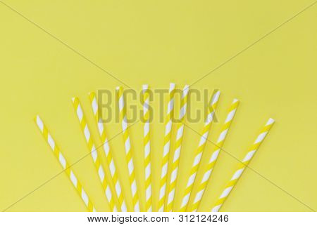 Fan Of Striped Paper Straws On A Yellow Background, With Copy Space