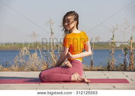 Yoga Outdoor. Happy Woman Doing Yoga Exercises, Meditate In The Park. Yoga Meditation In Nature. Con