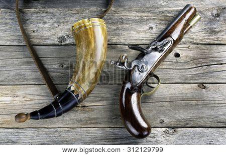 Antique English flintlock pistol and gunpowder horn made around 1800. poster