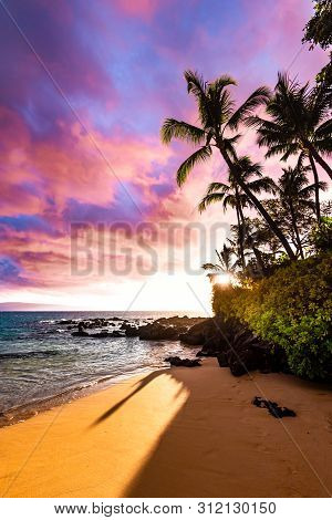 Tropical Island Paradise With Awesome Colorful Sky At Sunset And Calm Ocean Water Coming On Sandy Be