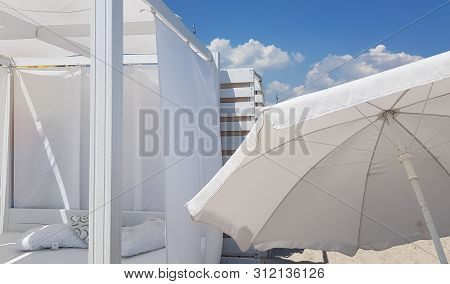 White Sunshade And White Parasol On Clear Beach Sand. Striped Wooden Wall Painted In White Color Wit