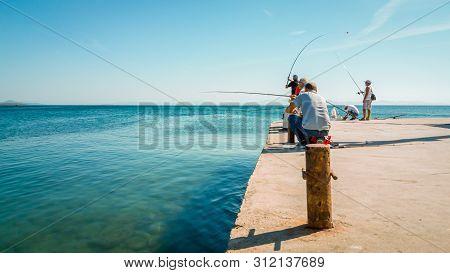 Didim, Turkey - October 03, 2017: Group Of People Fishing Under The Sun In Didim, Turkey. Leisure Co