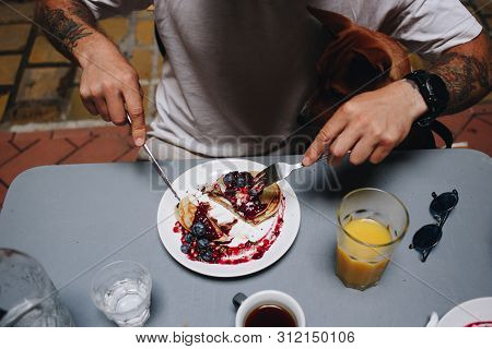 Man Cuts Pancakes With Berries On Plate At Local Cafe Or Restaurant During Healthy Tasty Breakfast W