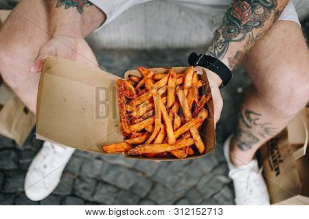 Cinematic Photo Of Hipster Millennial Man With Body Tattoos Hold Open Take Away Box Of Delicious Cri
