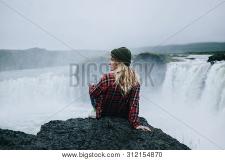 Beautiful Young Solo Female Adventurer Or Tourist Rests On Edge Of Cliff Or Mountain Overlooking Epi