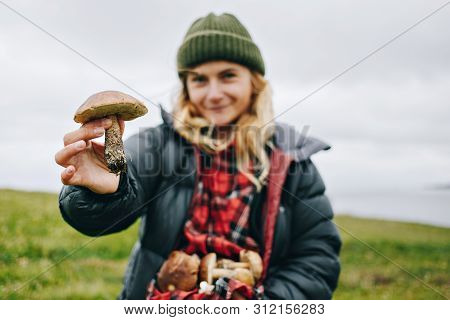 Young Beautiful Woman In Camping Outdoor Outfit For Cold Harsh Weather Holds Out Wild Fresh Picked M