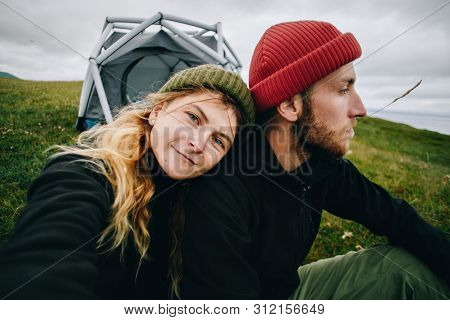 Cute Young Couple Of Millennial Or Generation Z Adventurers Or Travellers Sit In Front Of Tent, Girl