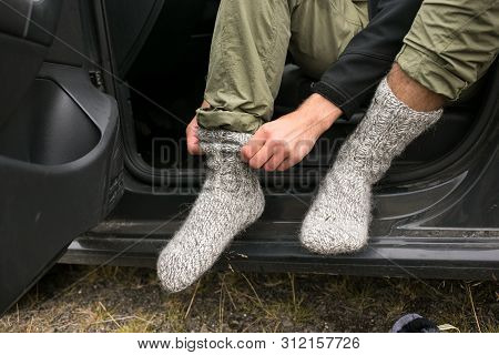Adventurer, Touirst Or Hiking Affectionate Changes Shoes Inside Car After Or Before Long Wet Walk In