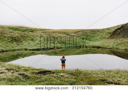 Silhouette Or Figure Of Man In Blue Sweater And Red Beanie Stand In Front Of Huge Glacier Lake On To