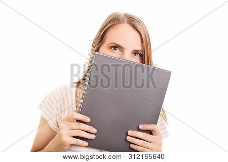 Beautiful Girl Hiding Her Smile Behind A Notebook, Isolated On White Background. Girl With A Mischie