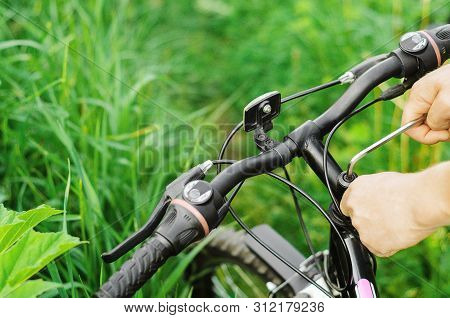 A Man Unscrews The Bolts With A Hex Wrench On The Handlebars Of A Mountain Bike Against The Backgrou