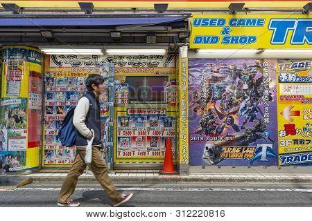 Tokyo, Japan - Mar 18, 2019: Man Walking Past A Japanese Game And Dvd Shop In Akihabara, Tokyo. It I