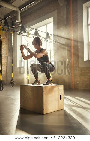 Challenging Myself. Side View Of Athletic Woman In Sportswear Doing Squat While Standing On Wooden B