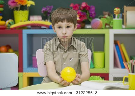 Sad Preschooler With A Ball In His Hands. Junior School Student At The Table With A Toy