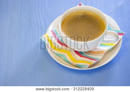 A cup of coffee with froth, white porcelain ceramics, color striped napkin. Blue wooden background. poster