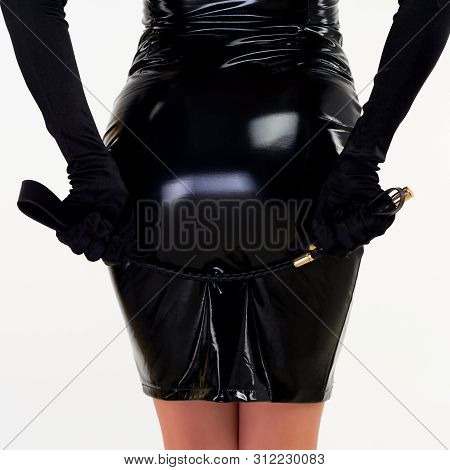 The Red-haired Passionate Lady In A Black Latex Dress Is Standing With Her Back Holding The Backside