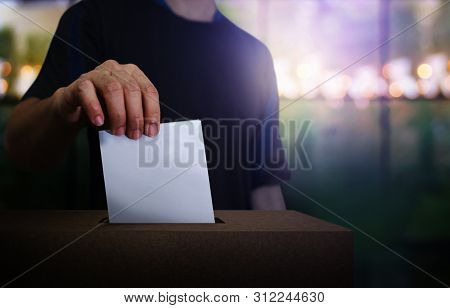Hand Holding Ballot Paper For Election Vote At Place Election Background. Election Vote Concept.vote