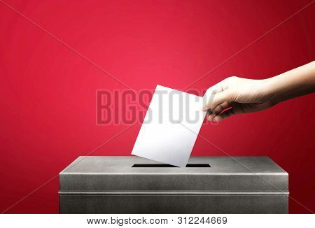 Hand Holding Ballot Paper For Election Vote Concept At Red Background.vote Is Very Important For Our