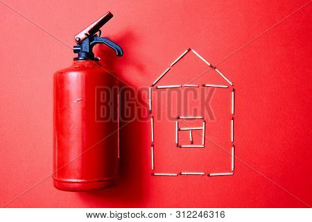 Fire Safety, Or Security And Protection Concept. Fire Extinguisher And The Figure Of The House Of Ma