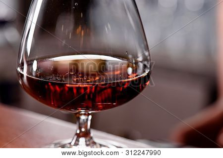 Glass Snifter With Cognac On A Wooden Bar Counter In A Restaurant Close-up. Handsome Male Drink In A