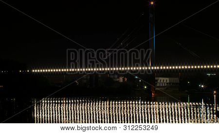 Night Time Lapse Shot Of A Railway Bridge Over The River. Lights Reflect On Water. Boats Pass.