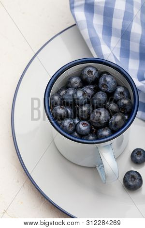 Close-up Of Fresh Blueberries In White Porcelain Cup. Background With Blue Tones.