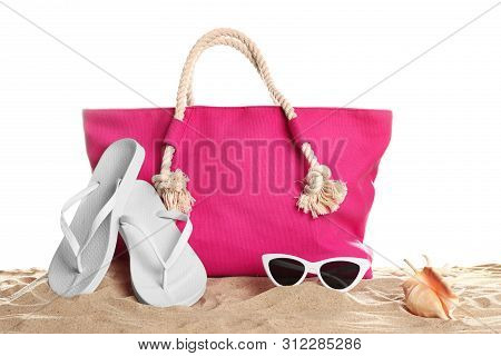 Stylish Coral Bag And Beach Accessories On Sand Against White Background