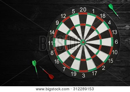 Dart Board With Color Arrows On Black Wooden Background, Top View