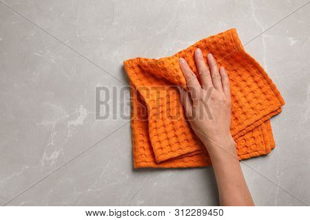 Woman Wiping Marble Table With Kitchen Towel, Top View. Space For Text