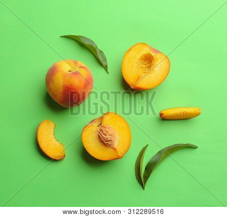Flat Lay Composition With Fresh Peaches On Green Background