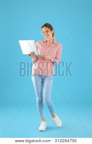 Full Length Portrait Of Young Woman In Casual Outfit With Laptop On Color Background