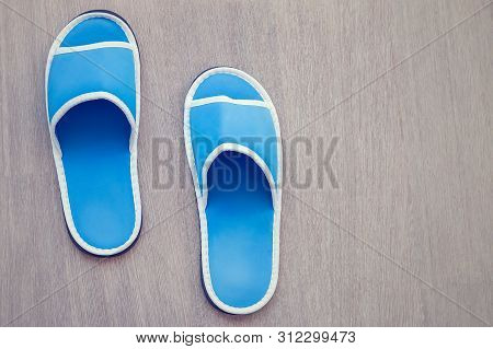 Blue House Slipper On Wooden Background. Soft Comfortable Home Slipper.