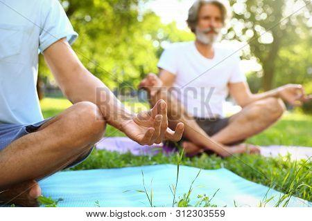 Men Practicing Morning Yoga In Sunny Park, Closeup